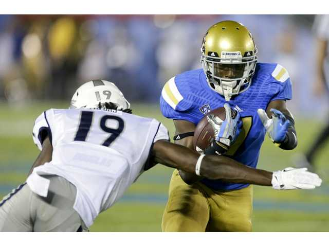 UCLA wide receiver Devin Fuller, right, runs past Nevada defensive back Evan Favors during the first half in Pasadena.