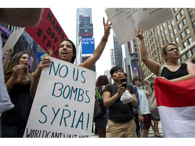 Rachel Lee Richards of New York. left, stands with opponents of a United States military strike against Syria as she and others protest at Times Square in New York Saturday.