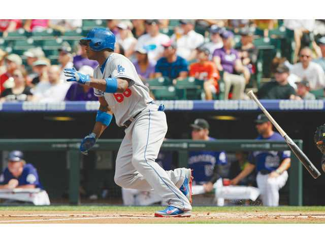 Los Angeles Dodger Yasiel Puig tosses his bat after singling against the Colorado Rockies in Denver on Monday.