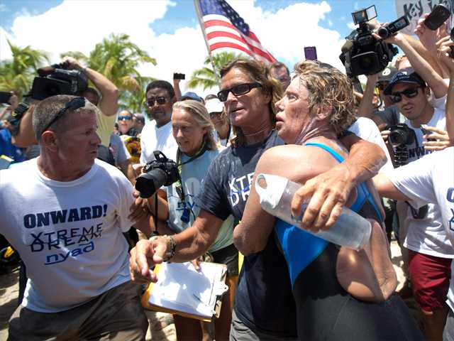 Endurance swimmer Diana Nyad, right, and her trainer, Bonnie Stoll hug after Nyad walks ashore Monday in Key West, Fla. after swimming from Cuba. Nyad became the first person to swim from Cuba to Florida without the help of a shark cage. She arrived at the beach just before 2 p.m. EDT, about 53 hours after she began her swim in Havana on Saturday.