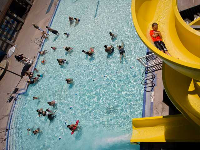 A boy takes a turn on the Ultimate Sidewinder II water slide at the Santa Clarita Aquatics Center as poolgoers swim in the water below.Photo by Charlie Kaijo for The Signal.