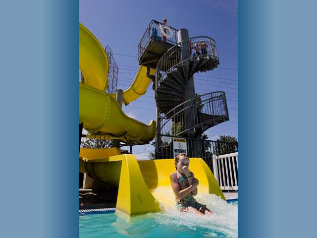 A young girl exits the Ultimate Sidewinder II water slide at the Santa Clarita Aquatics Center on Monday.Photo by Charlie Kaijo for The Signal.