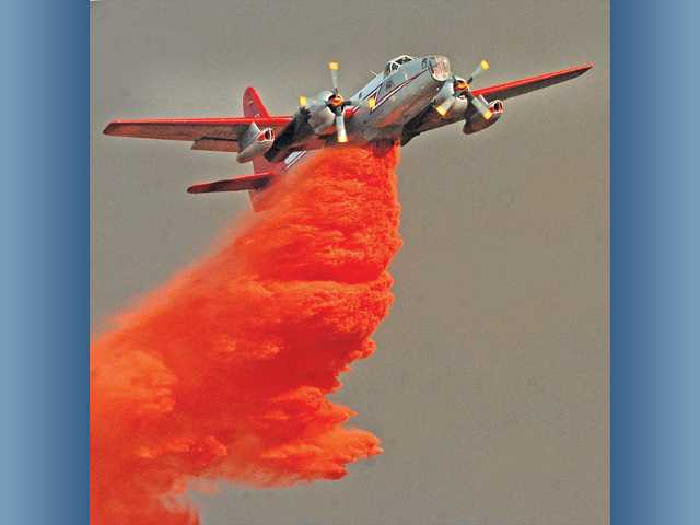 In this August 2009 file photo, a fixed wing aircraft maks a drop of fire retardant near a home while battling the Station Fire near in Acton. Photo by Dan Watson.