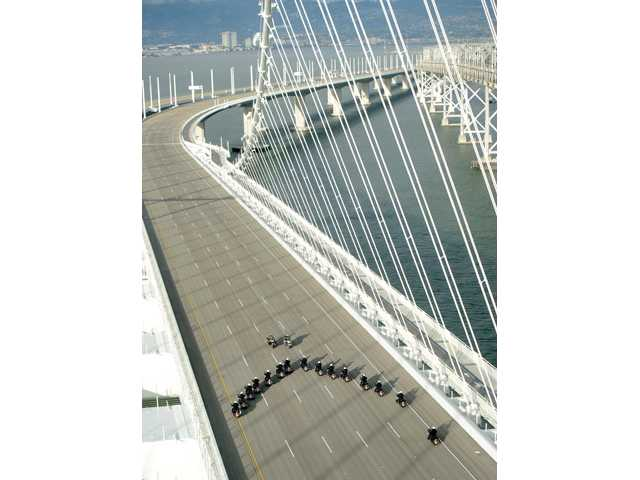 In this photo provided by the Bay Area Toll Authority, a phalanx of police officers cross the San Francisco-Oakland Bay Bridge on Monday after leading a procession marking the east span's opening, in San Francisco.