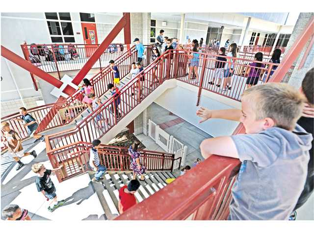 A fourth-grader, right, waves to his classmates as they head down the stairs to the playground at Emblem Academy in Saugus on Wednesday. Signal photo by Dan Watson