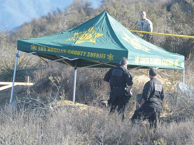 Bomb technicians and sheriff's deputies search for evidence Wednesday around a sheriff's tent that covers a burned body off Lake Hughes Road a few miles above the Castaic Lake main boat launch area. Signal photo by Dan Watson