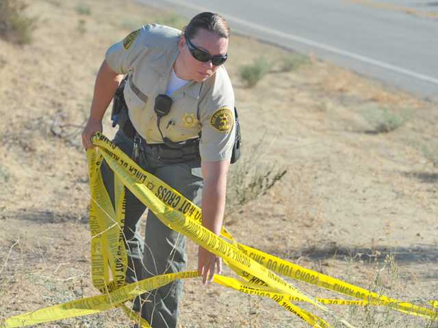 A deputy collects crime scene tape at the scene of a burned body found in Castaic early today by a passing cyclist. Signal photo by Dan Watson