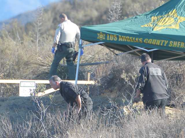 A deputy and members of the bomb squad search the area around a burned body found off Lake Hughes Road in Castaic early today. Bomb squad members are called in to the scene of burned bodies to search for signs of arson. Signal photo by Dan Watson