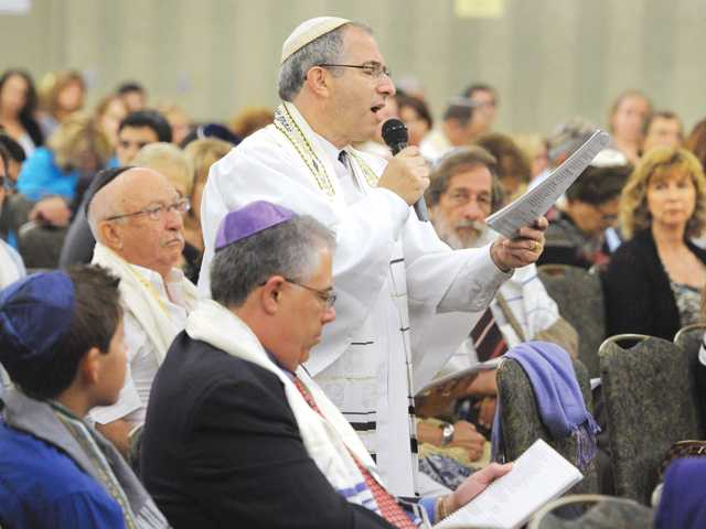 Cantor Kenny Ellis walks down the aisle as he sings The Hazzan's Prayer amid hundreds of attendees during the Rosh Hashana service hosted by Temple Bet Ami held at the Hyatt Regency Valencia on Thursday. Photo by Dan Watson.