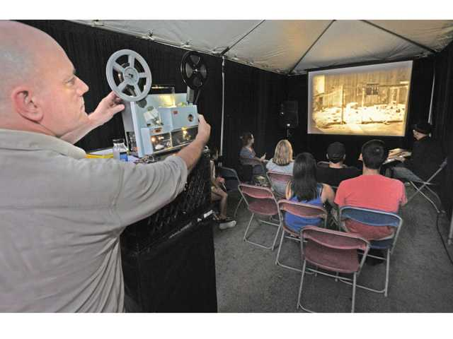 Tom Barns of Retroformat threads the projector to show an 'Our Gang' comedy as Cliff Retallick, right, performs live accompaniment for the audience during the Film SLAM event in Old Town Newhall on Thursday night. Photo by Dan Watson.