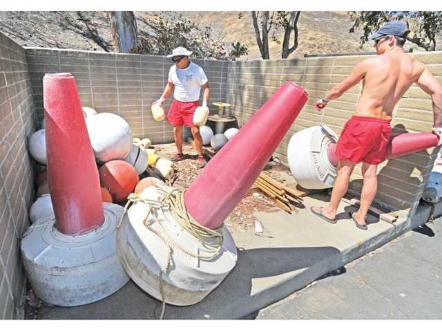 Senior Lifeguard Oscar Villagomez, left, and lifeguard Tyler Miller stow away navigation buoys used in the swim beach area of the lower lagoon to mark the end of summer season at Castaic Lake. Signal photo by Dan Watson