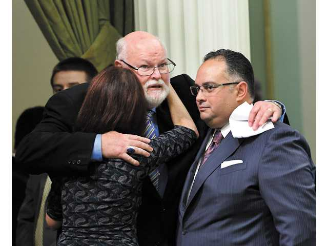State Sen. Jim Beall, D-San Jose, center, hugs Assemblywoman Nancy Skinner, D-Berkeley, and Assembly Speaker John Perez, D-Los Angeles after his childhood sexual abuse bill was approved by the Assembly at the Capitol in Sacramento.