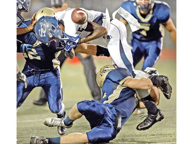 West Ranch's Trevor Aleshire forces a fumble by Sierra Canyon's Eric Markes at Valencia High School on Friday night.