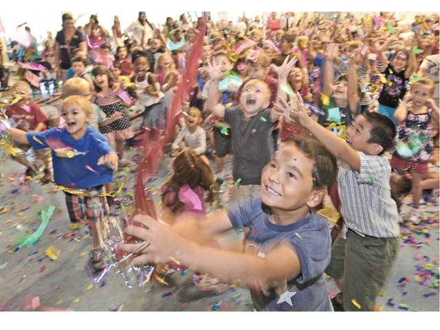Students at Northlake Hills Elementary School chase confetti as the student body and faculty gather in the multi-purpose room for the 10th anniversary celebration of the school in Castaic on Friday.