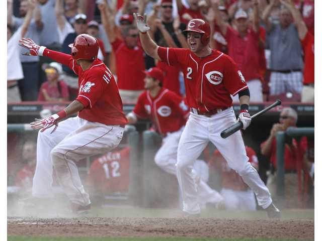 Cincinnati Red Billy Hamilton, left, scores the winning run at home against the Los Angeles Dodgers on Saturday in Cincinnati.
