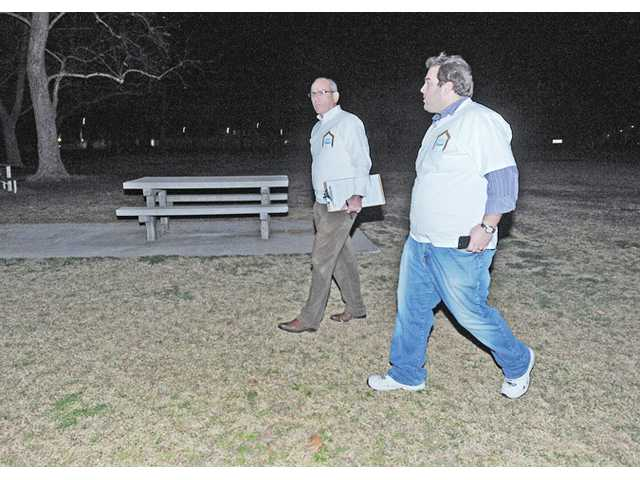 Bret Wims, center, and Jason Abrahamson walk through a darkened Valencia Meadows Park as they participate in a former Greater Los Angeles Homeless Count.