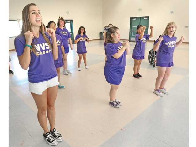 Valencia High School student Julia Competelli-Pizza, left, leads the special needs members of the Valencia Viking Star Cheer club in practice at the Valencia High School multipurpose room during lunchtime Thursday.