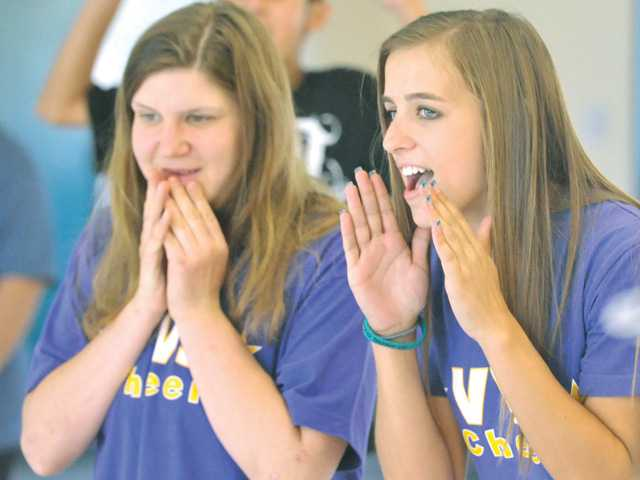 Valencia Viking Star Cheer team member Kayla Davidson, left, gets some coaching from Valencia High School student Julia Competelli-Pizza as members of the special needs cheer team practice on Thursday.