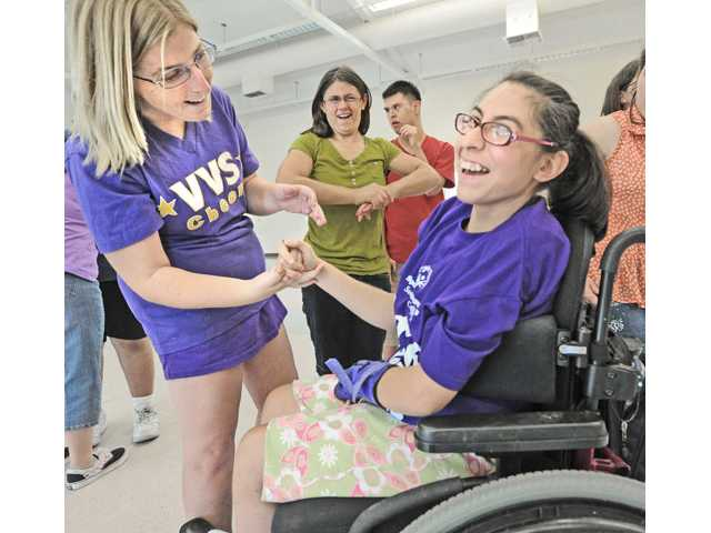 Valencia Viking Star Cheer team members Allie Hill, left, and Jessica Cervacio celebrate after their special needs cheer team practiced at Valencia High School on Thursday.