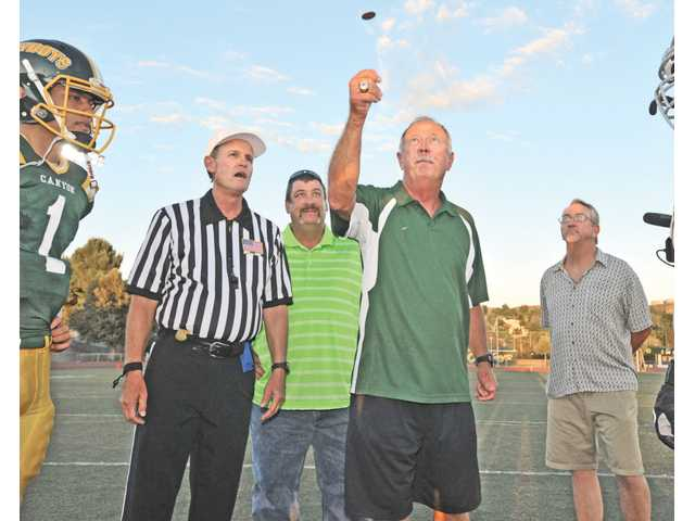 Refferee Fred Tanner calls for the coin toss as former Canyon High head football coach Harry Welch, center, flanked by 1983 Canyon High CIF championship team captains Tony Moore, left, and Rick Burton, flips the coin at the Canyon High School football game on Saturday.