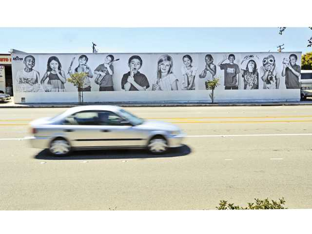 The ARTree's Ever-Changing Mural displaying the images of 12 children on the 90 foot vinyl photograph was installed on Railroad Avenue near 9th Street in Newhall on Saturday. Two additional 30 foot panels are displayed on either side of the cinder block building.