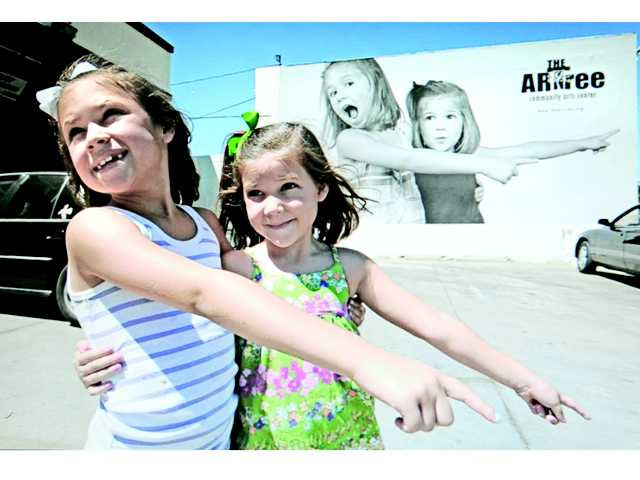 Madison Hernandez, 7, left, and her sister Malia, 5, duplicate their pose for a parent's photo as it appears on the 30-foot panel of the ARTree Ever-Changing photo mural behind them on Railroad Avenue in Newhall on Saturday.
