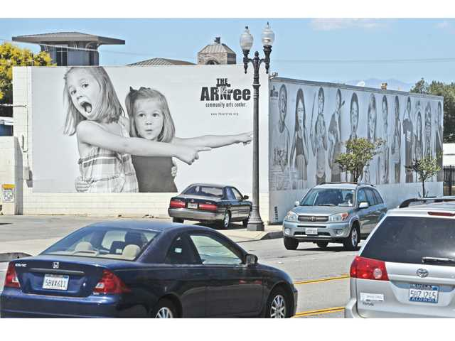 A 30-foot panel is displayed on one side of the cinder block building on Railroad Avenue in Newhall on Saturday.