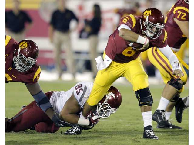 USC quarterback Cody Kessler, right, is tackled by Washington State nose tackled Ioane Gauta din Los Angeles on Saturday.