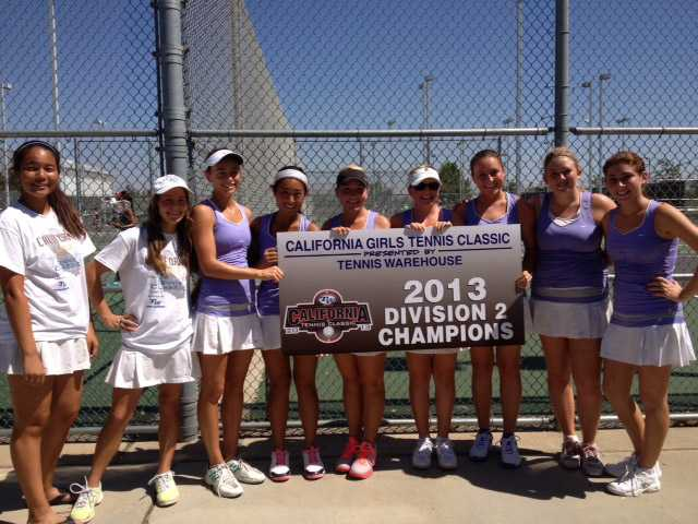 The Valencia girls tennis team poses with a championship banner after winning the 2013 California Tennis Classic Division II title.