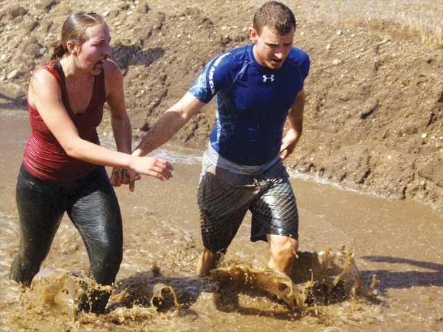 A pair of runners hold hands as they slog through a pool of muddy water toward the end of the 4-mile course at the 18th annual SEB Mud Run on Sunday in Castaic. Photo by Jim Holt.
