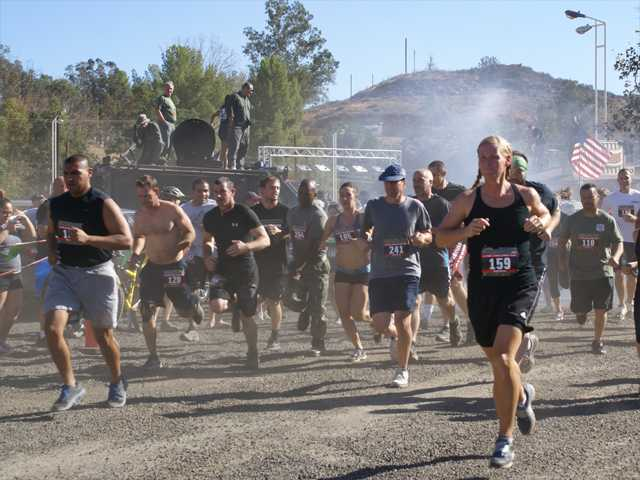 A crowd of mud runners take off as SWAT officers look on from atop an armored SWAT vehicle on Sunday in Castaic. Photo by Jim Holt.