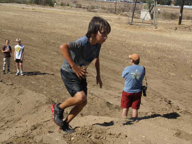 Los Angeles resident Landon Barragan, 9, runs up a hill after a trip through a pit of muddy water during the SEB Mud Run on Sunday in Castaic. Barragan reportedly came in second place in the 4-mile race, finishing faster than all but one of the adults who ran the course. Photo by Jim Holt.