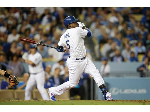 Los Angeles Dodger Juan Uribe hits his third home run during a game against the Arizona Diamondbacks on Monday in Los Angeles.