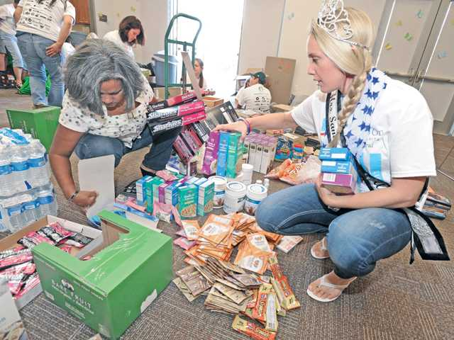 Volunteer Silvia Sellen, left, and Rachel Ward gather donated food and toiletries as their prepare to fill care packages for local firefighters during the HandsOn Santa Clarita 9/11 Day of Service and Remembrance held at the Newhall Library on Wednesday. Signal photo by Dan Watson