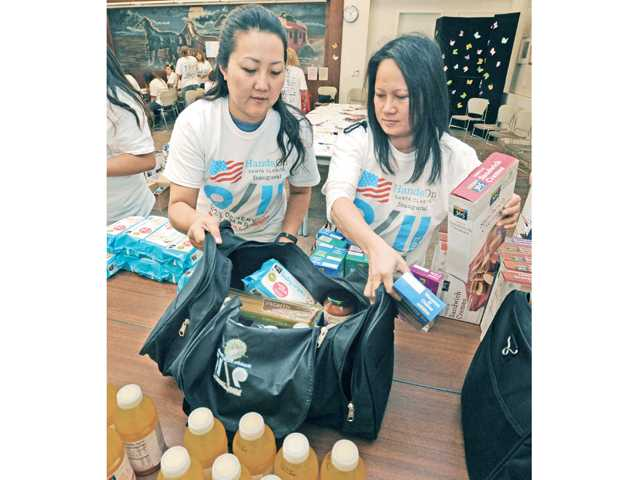Volunteers Kristina Carnes, left, and Hnh Tran fill care packages for local firefighters during the HandsOn Santa Clarita 9/11 Day of Service and Remembrance at Newhall Library on Wednesday. Signal photo by Dan Watson