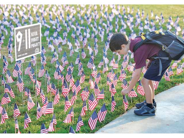 Trinity Classical Academy first-grader John Hunter straightens one of the 2,977 American flags on the school's front lawn today honoring 9/11 victims. Signal photo by Dan Watson
