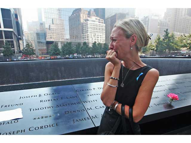 Carrie Bergonia of Pennsylvania looks over the name of her fiancé, firefighter Joseph Ogren, at the 9/11 Memorial during ceremonies marking the 12th anniversary of the 9/11 attacks on the World Trade Center in New York on Wednesday.