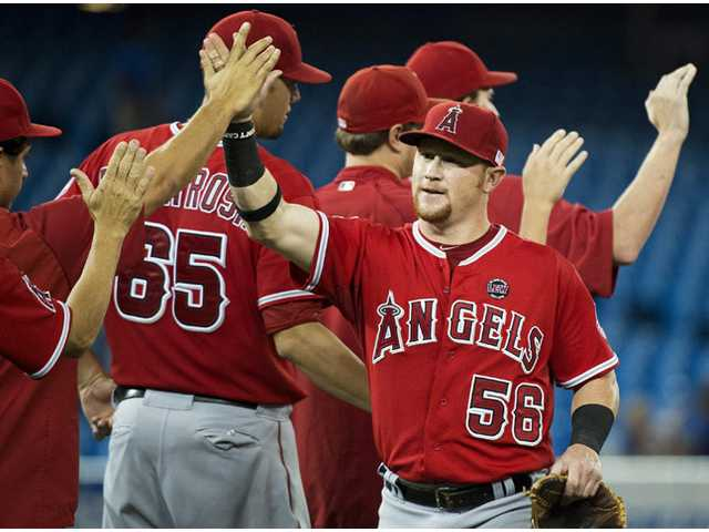 Los Angeles Angels right fielder Kole Calhoun, right, celebrates with teammates after they defeated the Toronto Blue Jays in Toronto on Wednesday.