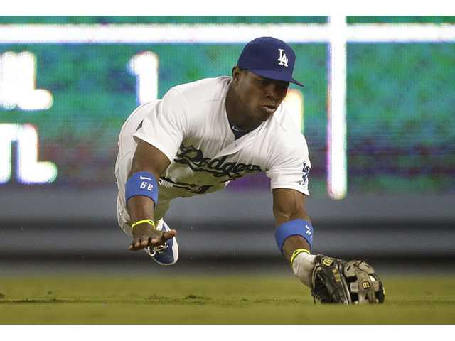 Los Angeles Dodgers' Yasiel Puig catches a ball hit by Arizona Diamondbacks' Chris Owings on Wednesday in Los Angeles.