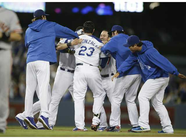 Los Angeles Dodger Adrian Gonzalez, center, is congratulated by teammates after Gonzalez hit a walk-off single against the San Francisco Giants on Thursday in Los Angeles.