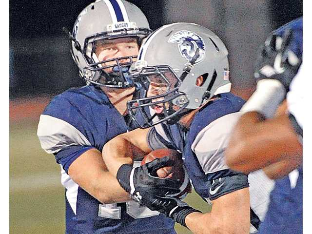 Saugus quarterback Chris Hamilton, left, hands off to Blake Austin, who goes in for the touchdown against Buena at Canyon High on Thursday.