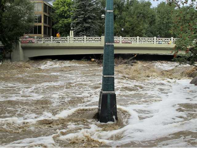 Rain-swollen Boulder Creek flows around a marker that shows historic flood levels on Friday morning in Boulder, Colo.