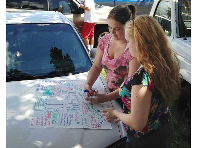 In this Sept. 10 photo, Summer Howard, 19, and Alecia Wilkins, 18, make a poster for Summer's sister Rebecca Sedwick.