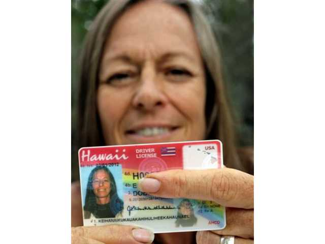 "Janice ""Lokelani"" Keihanaikukauakahihulihe'ekahaunaele holds her Hawaii drivers license that lacks the space for her full name. Friday, Sept. 13, 2013 in Ocean View, Hawaii."