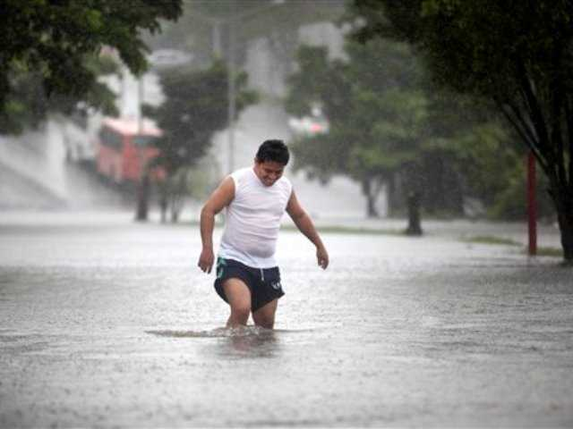 A man walks through a flooded street during heavy rains caused by Tropical Storm Ingrid in the Gulf port city of Veracruz, Mexico, Friday Sept. 13., 2013.