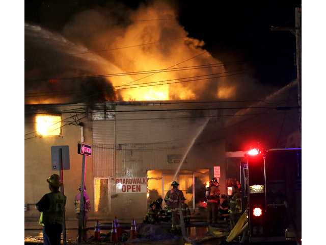 Firefighters battle a blaze in a building on the Seaside Park boardwalk on Thursday in Seaside Park, N.J.