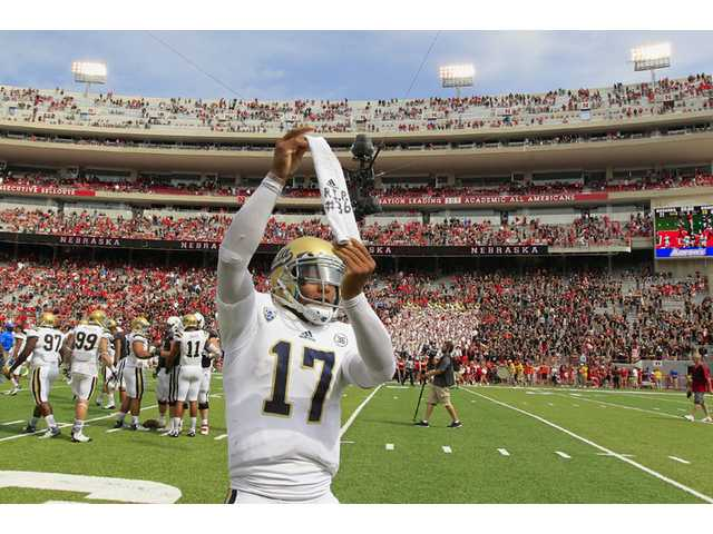 UCLA quarterback Brett Hundley (17) pays homage to deceased teammate UCLA wide receiver Nick Pasquale (36) after UCLA beat Nebraska on Saturday in Lincoln, Neb.