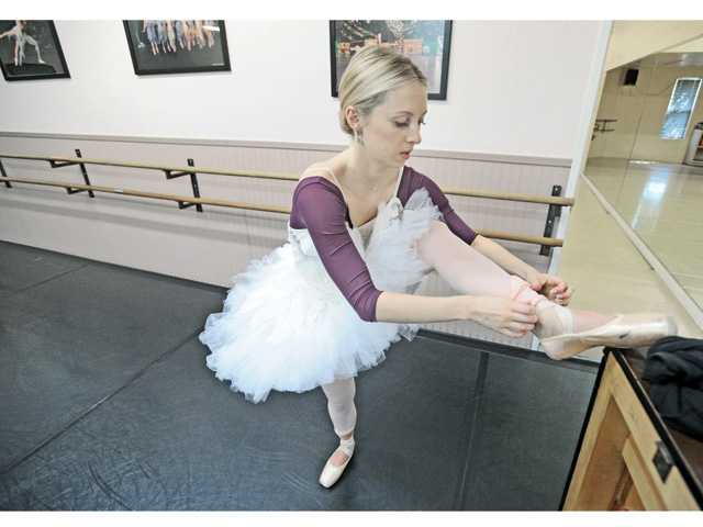 "Ballerina Season DeAngelis as Odette, the Swan Queen, ties her point shoes as she prepares to rehearse ""Swan Lake"" at the Santa Clarita Ballet Academy in Canyon Country."