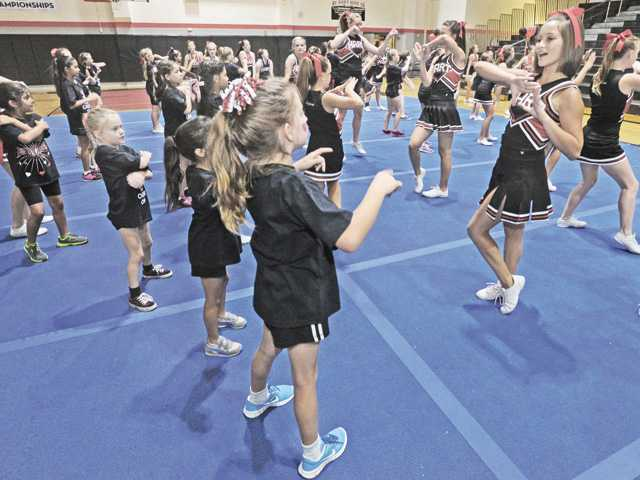 Hart High School cheer leader, Tiffany Kaplan, right, leads her group of young cheer camp participants at the Hart Cheer Spirit Day held at Hart High School in Newhall on Saturday.