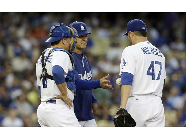 Los Angeles Dodgers manager Don Mattingly takes the ball from starting pitcher Ricky Nolasco as catcher Tim Federowicz.